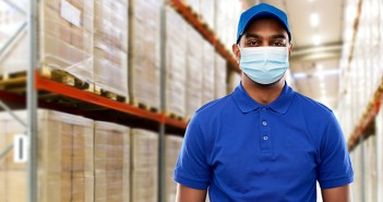 indian delivery man in medical mask at warehouse