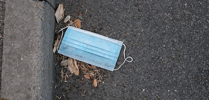 A disposable face mask discarded in the gutter during the COVID1